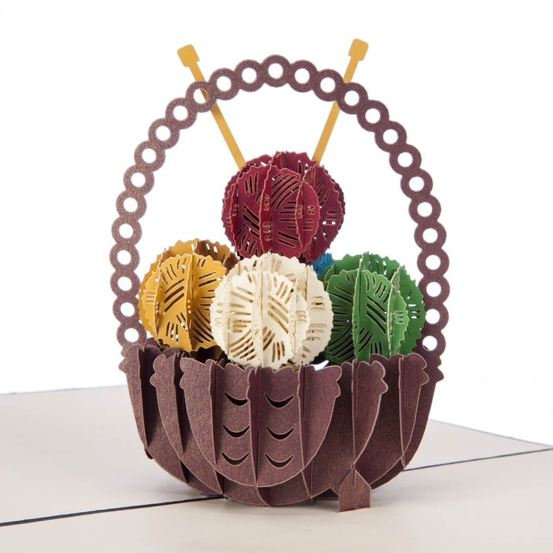 Close up image of knitting pop up card featuring a 3D basket filled with balls of yarn and some knitting needles