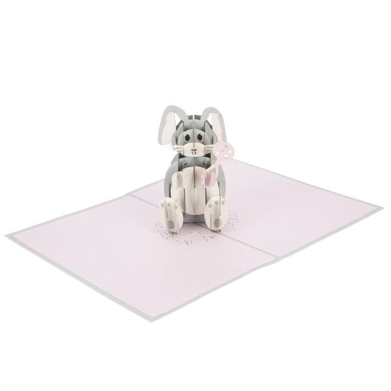 new baby girl pop up card featuring a 3D grey and white bunny holding a pink rattle when opened fully