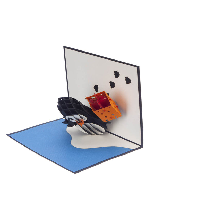 penguin pop up birthday card featuring a 3D penguin holding a birthday present, half open at 90 degrees