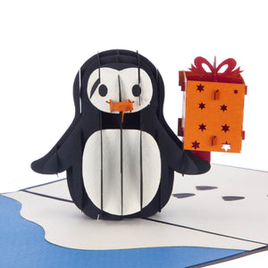 close up image of penguin pop up birthday card featuring a 3D penguin holding a present