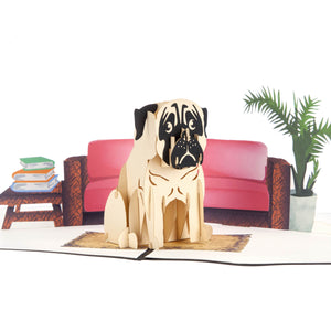 Close up image of Pug Pop Up Card featuring a white and black 3D pug sitting on a matt in front of a stylish red 2D sofa