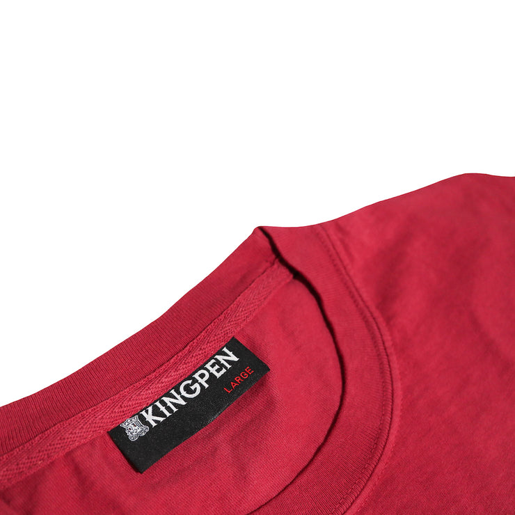 A detailed look at the collar of the Kingpen Heritage Collection Est. LA Short Sleeve shirt. The collar is sewn into the bottom of the collar, and is black. The writing on it shows the Kingpen wordmark with King's Head logo in white. Underneath is the size of the shirt in red.