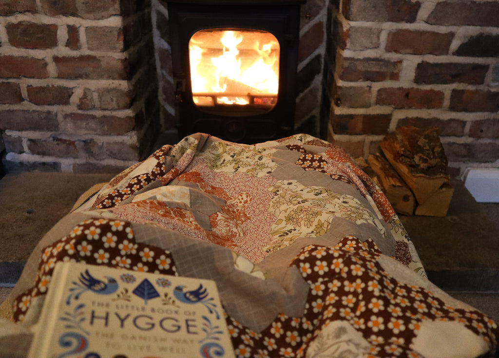 """alt=""""cosy patchwork quilt with wood stove and the little book of hygge by Bramble and Fox UK hygge cottagecore shop"""""""
