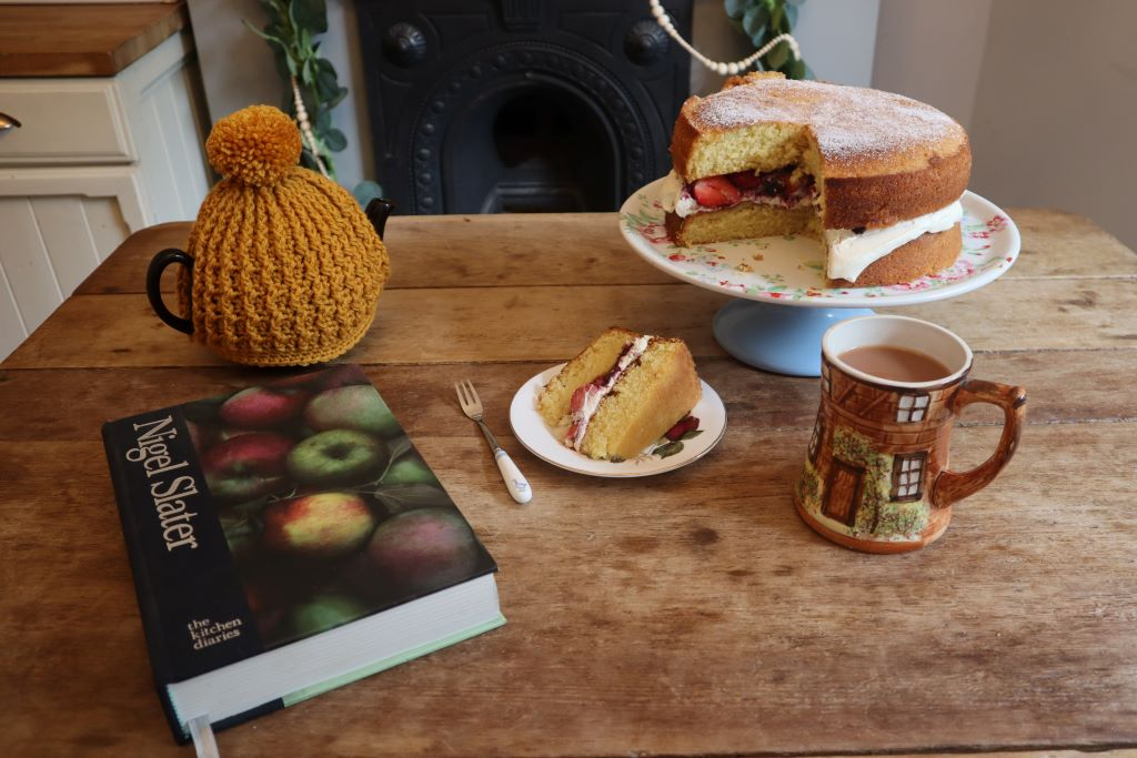 """alt=""""cosy tablescape of teapot, cake, mug and book from Bramble and Fox Uk Hygge shop and blog"""""""