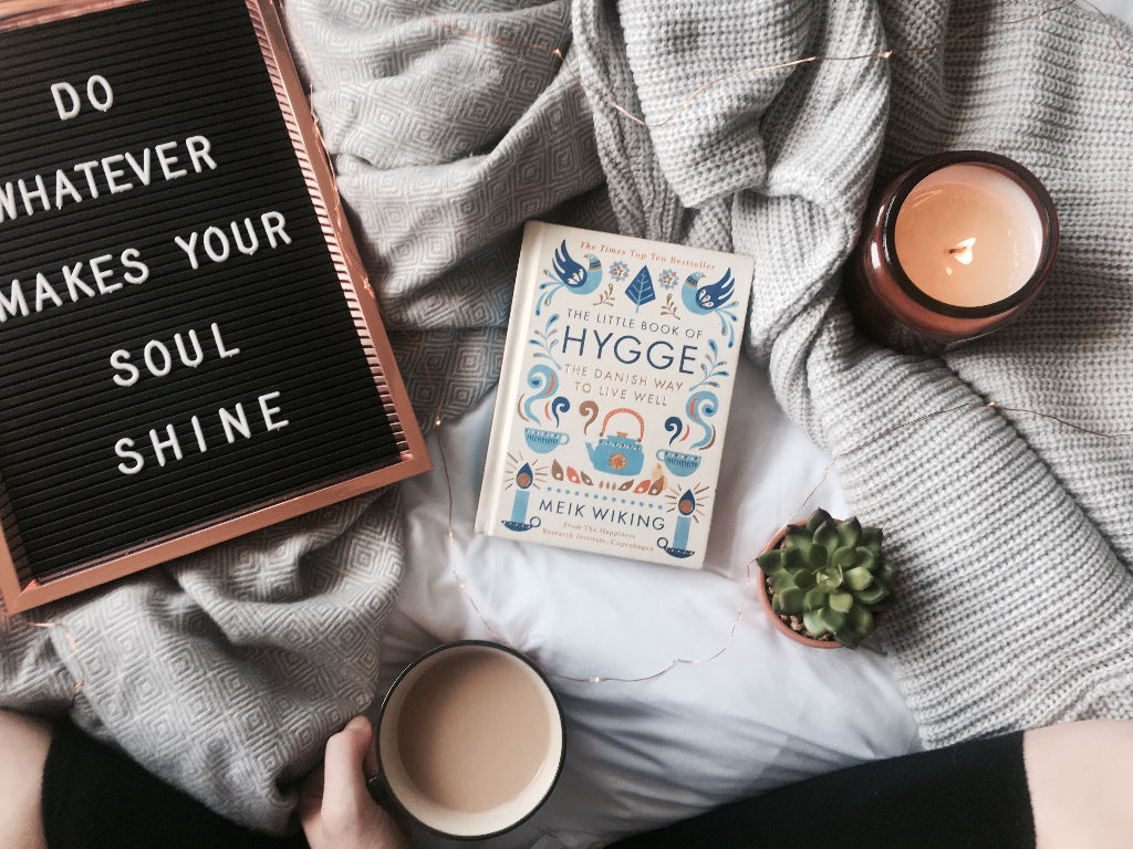 "alt=""the little book of hygge flatlay with candles and tea, bramble and fox collab with the slow living guide"""