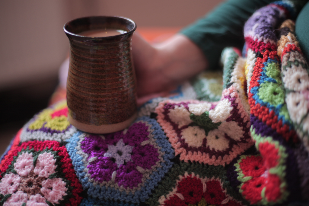 "alt=""multi coloured crochet hexagon blanket and handmade pottery mug by bramble and fox uk cottagecore shop"""