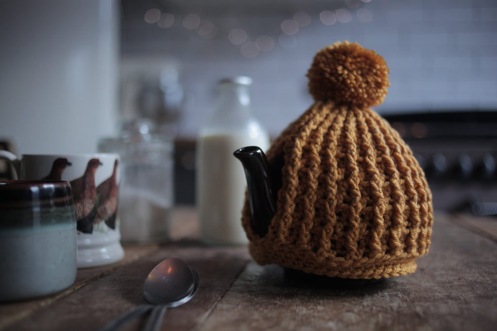 mustard hand crochet chunky knit tea cosy with pom pom made by Rosie and Max Crafts