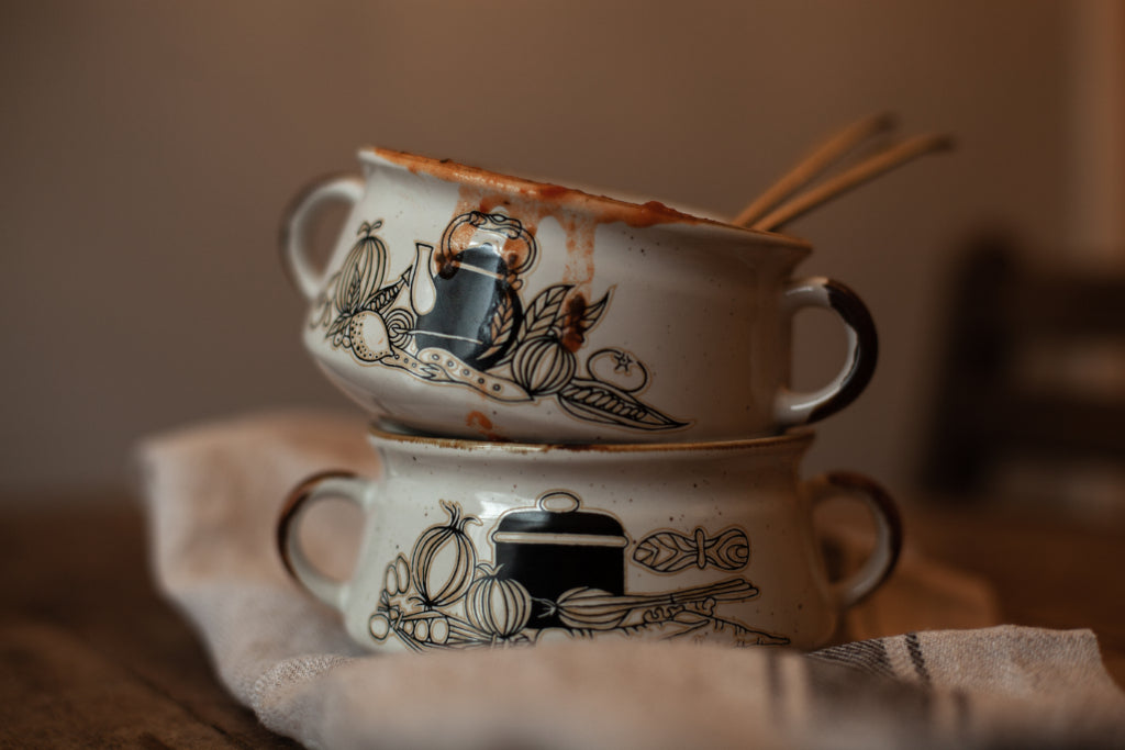 "alt=""pair of vintage soup bowls with handles and motif of rustic veg and stove kettle by bramble and fox uk hygge shop"""