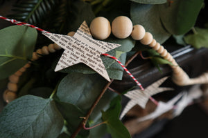 Close up of a paper star garland. Hand-cut stars from 'A Christmas Carol' and vintage sheet music hang from candy stripe baker's twine. Made by Bex Massey of Bramble and Fox