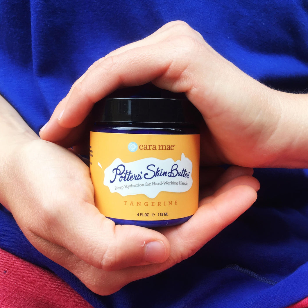 4 ounce jar of tangerine hand cream cradled by hands