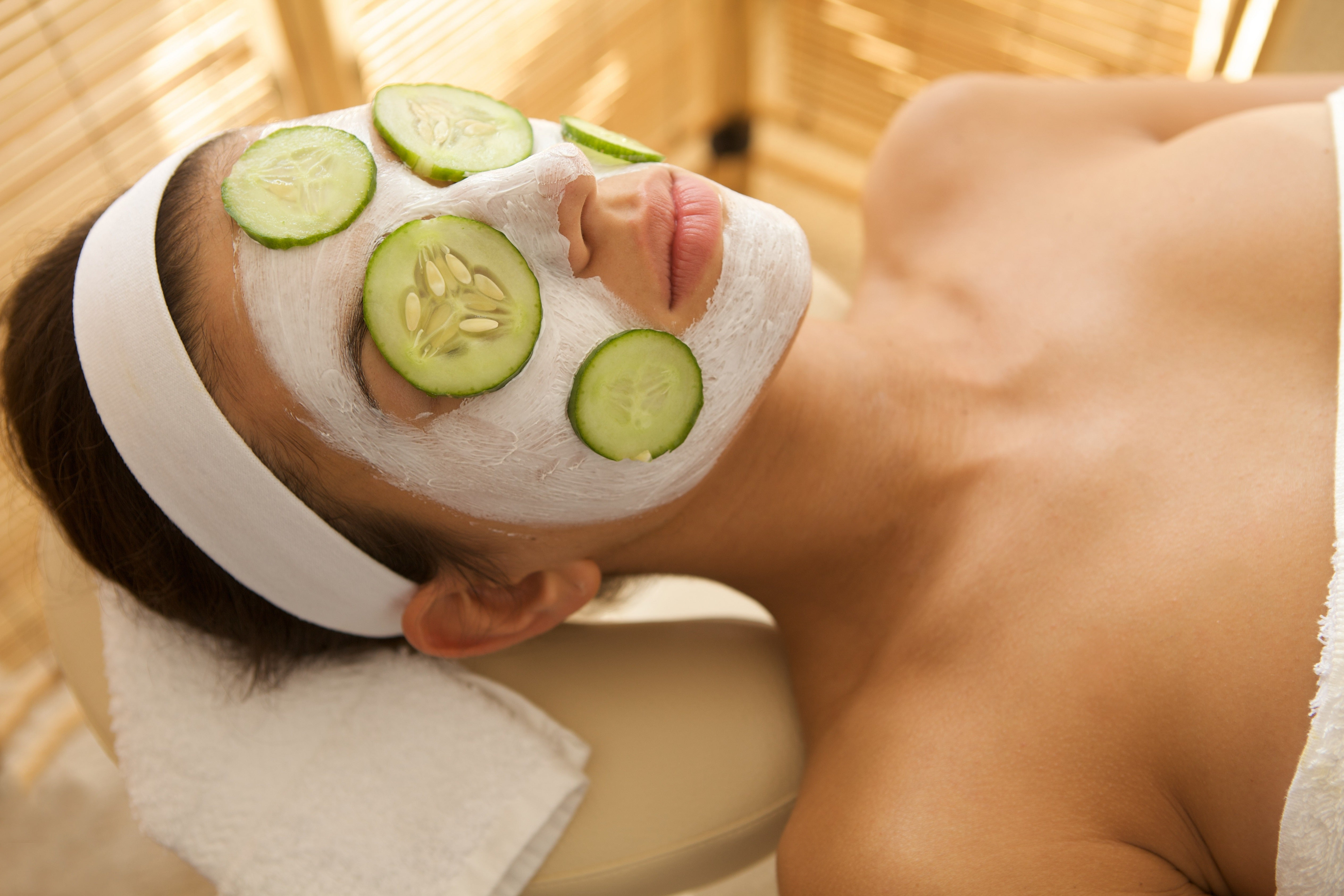 woman with applied facial mask cream and cucumber on face