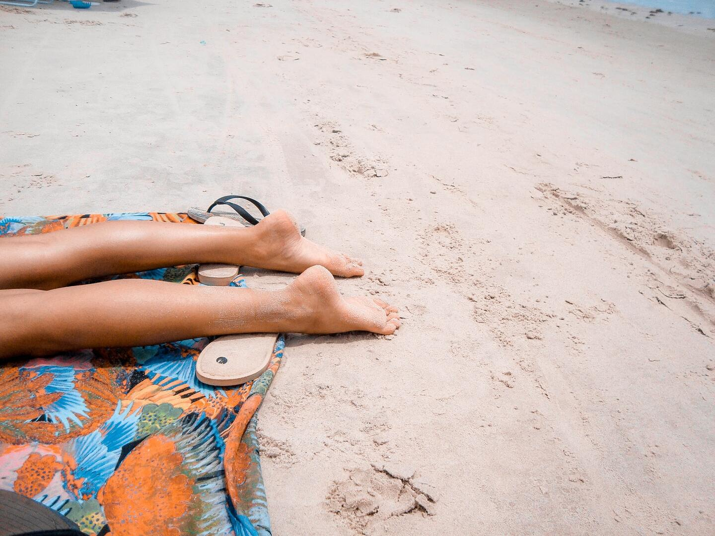 legs of a woman and sandals on the ground