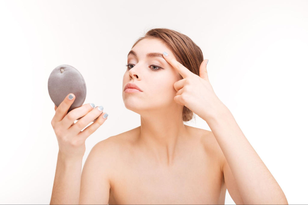 woman holding a compact mirror