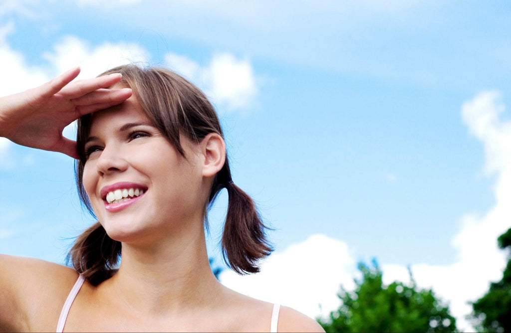 smiling woman dazzled in sunlight
