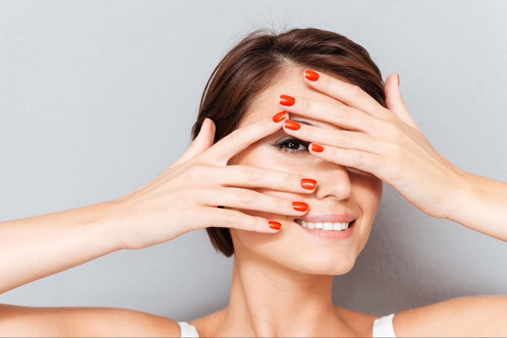 woman concealing her face through her hands