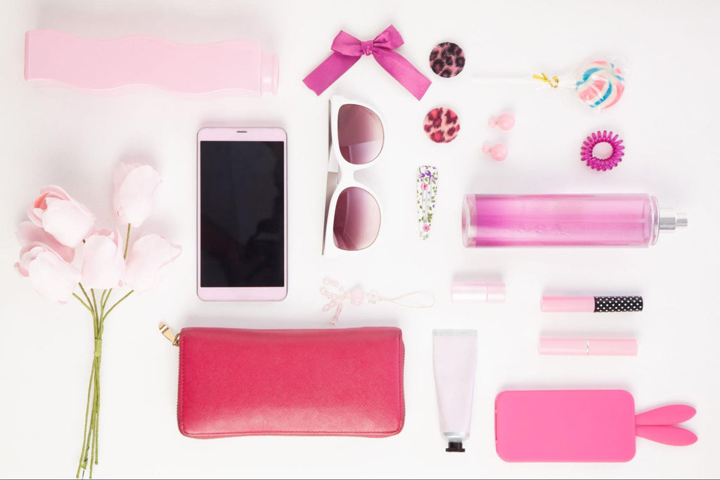 phone, sunglasses, perfume and other accessories of a woman