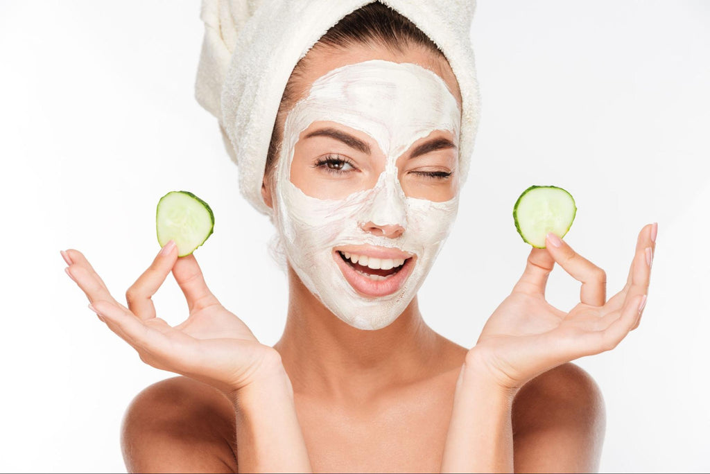woman with facial mask holding cucumber