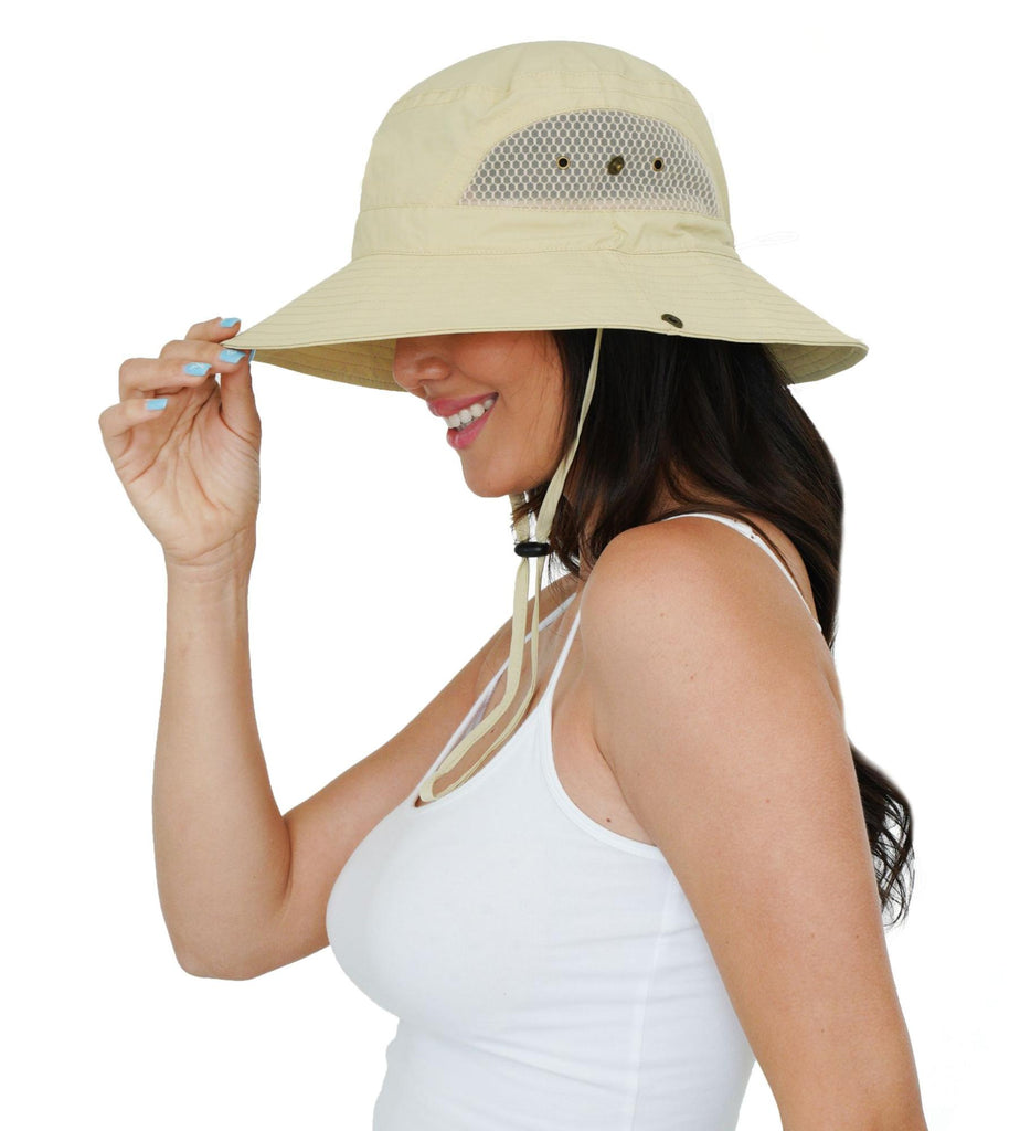 sideview of a woman holding her hat on head