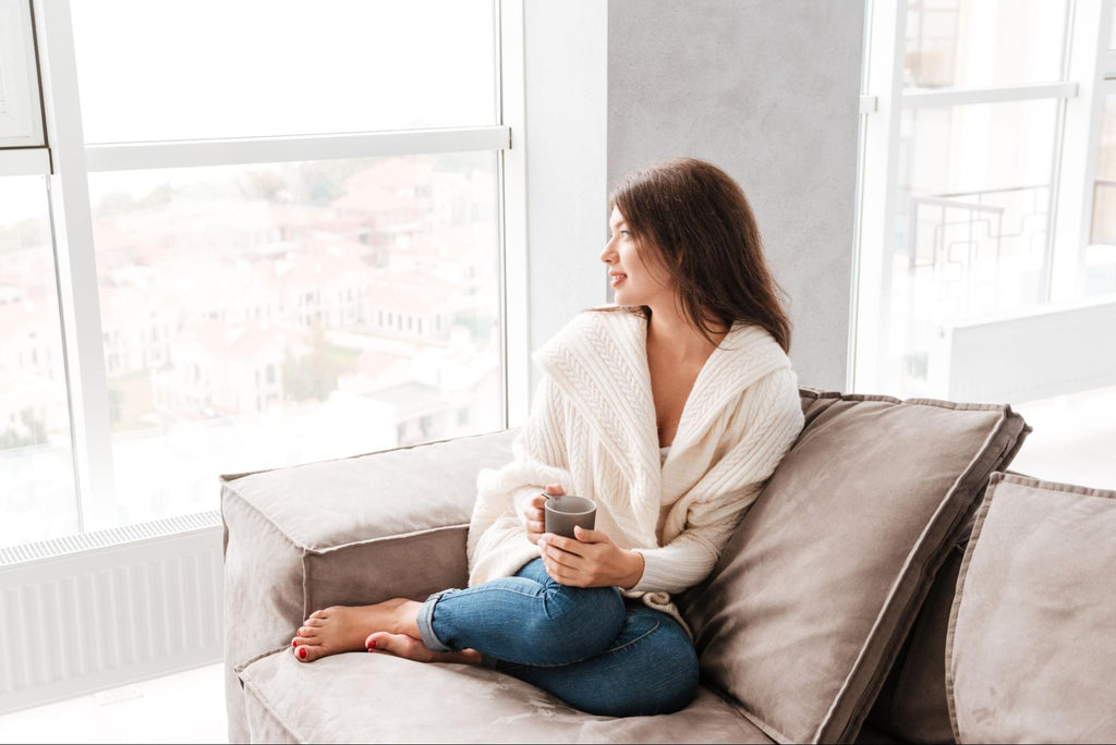 woman sitting on a couch while holding a cup of coffee