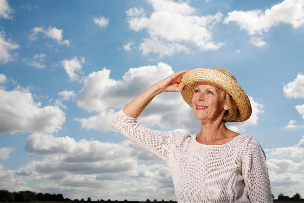 woman holding her hat on her head