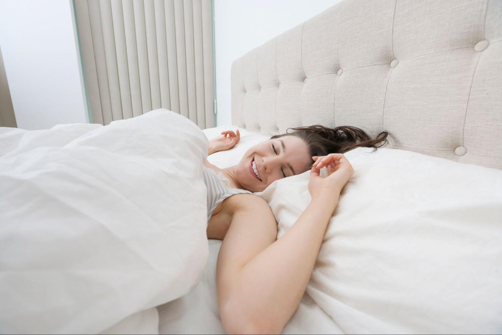 smiling woman laying in white bed