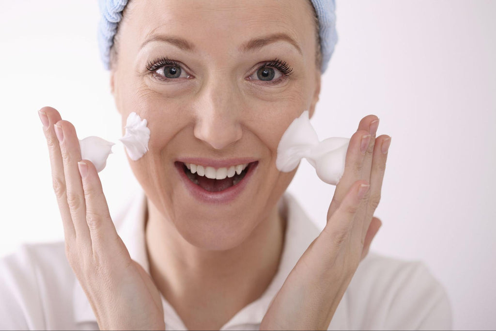 woman cleansing her face with facial foam