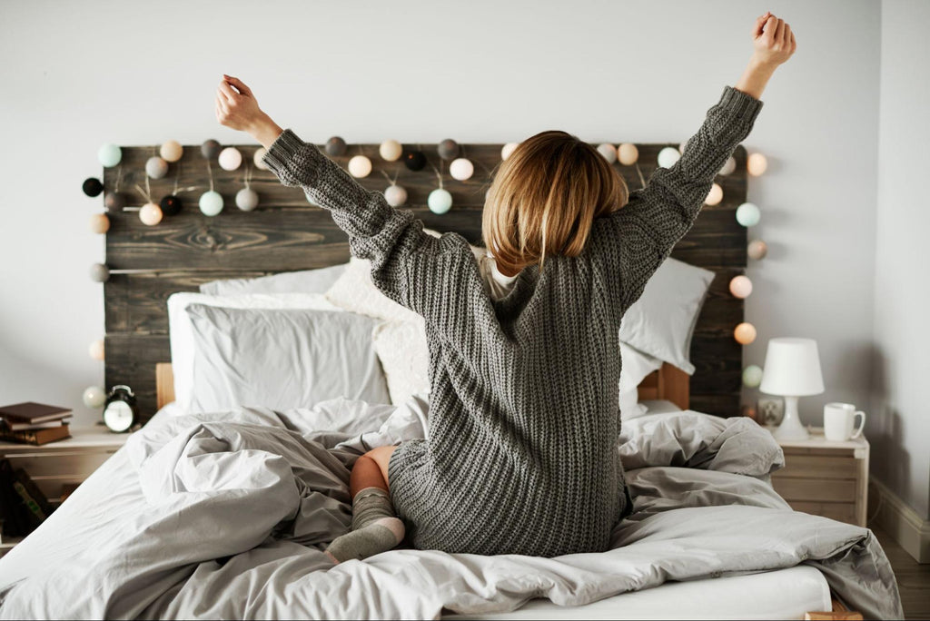 woman on bed stretching her arms
