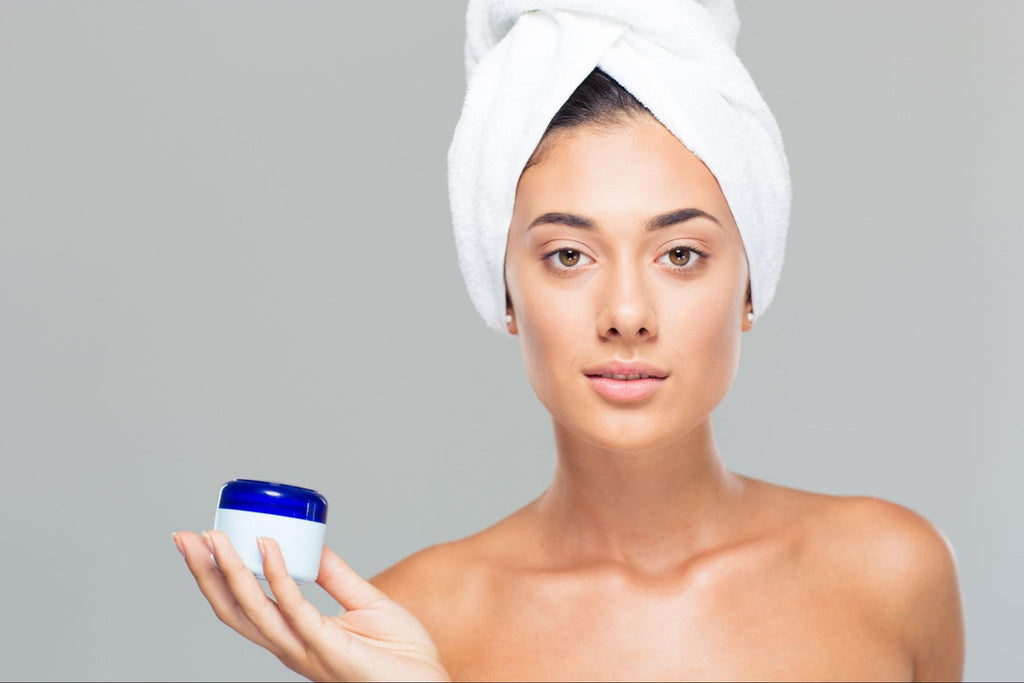 woman with a white towel on her head, holding a moisturizer