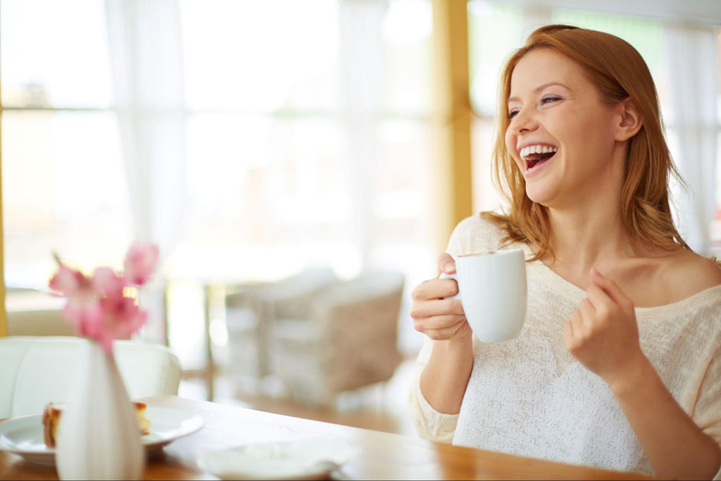 laughing woman while holding a cup
