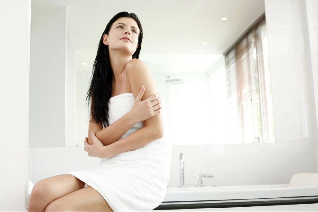 woman on a bathroom, wrapped with a white towel holding her arms
