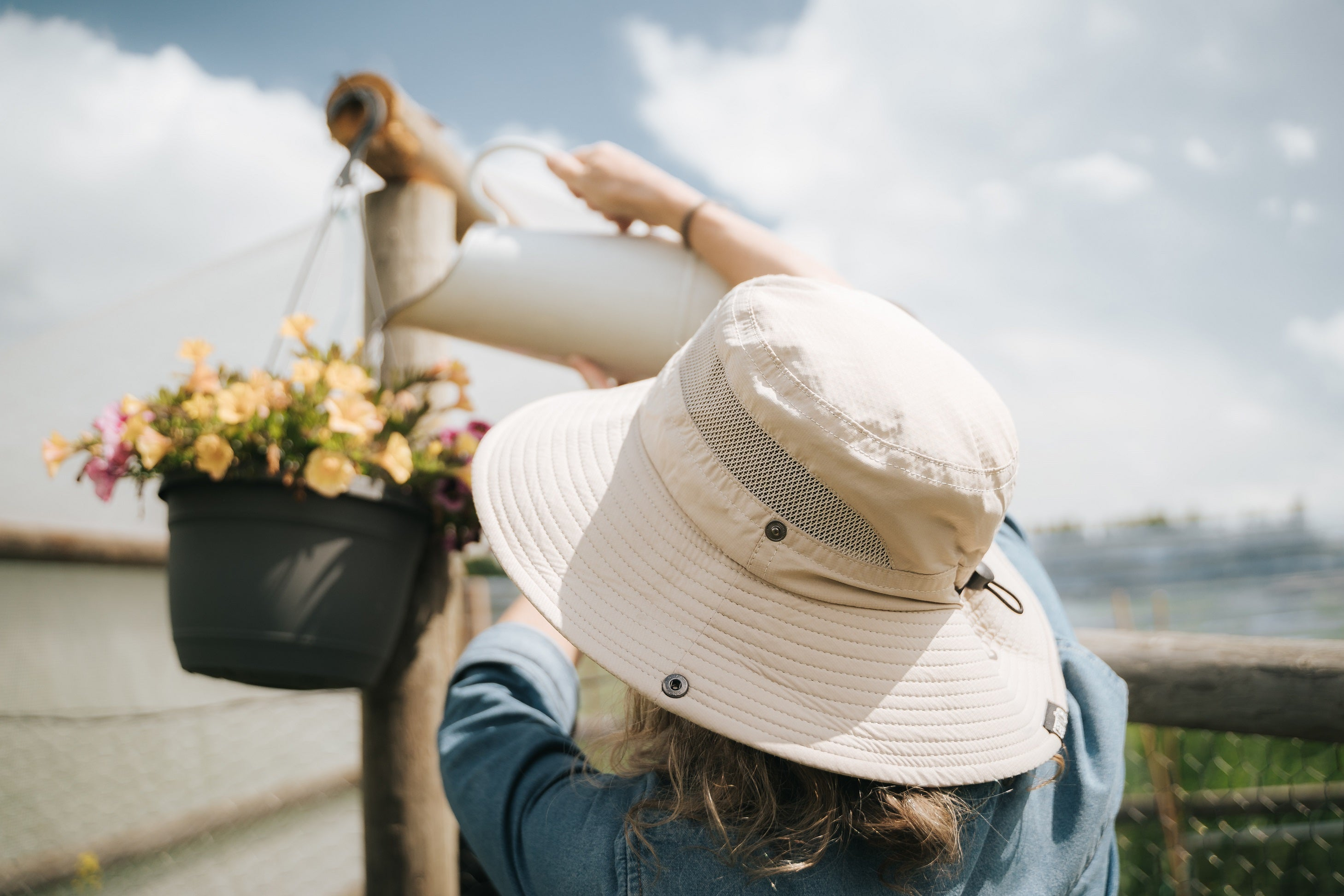 woman watering her plants under the sun