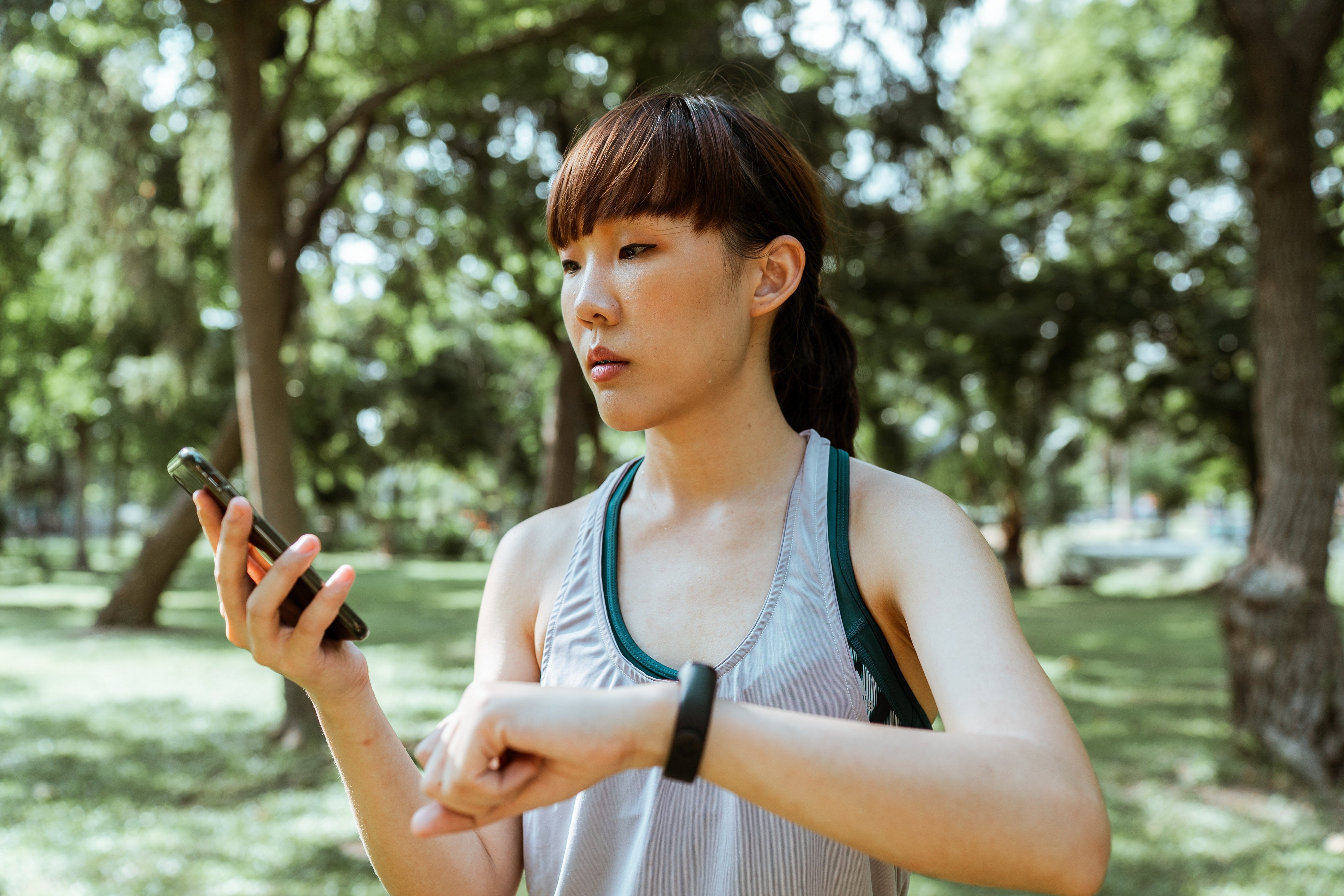 woman checking her smart watch on her phone app