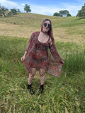 girl in field with mesh dress and kimono for music festival vintage 70s style
