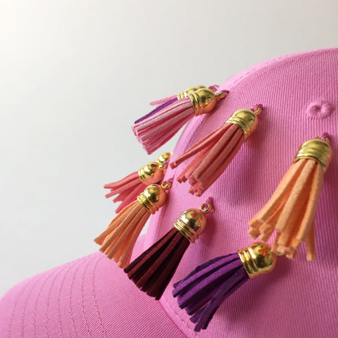 pink cap with multi colored rainbow tassels