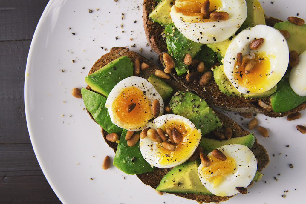 toast topped with avocado, hard boiled eggs, and sunflower seeds