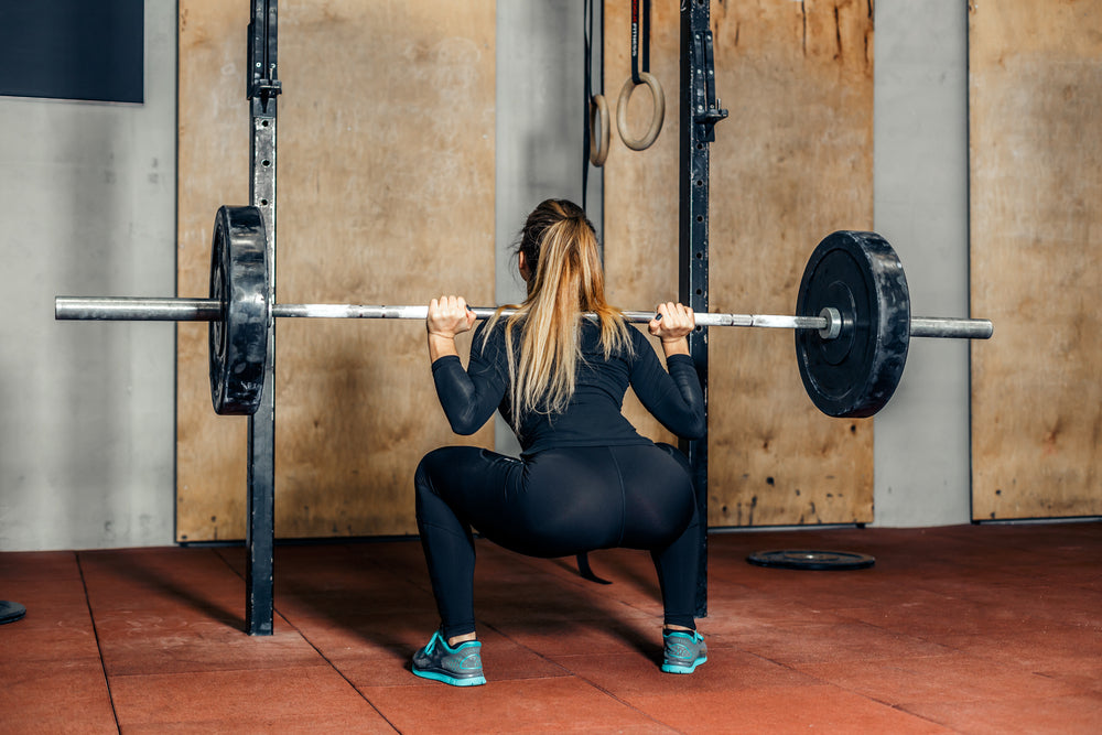 Leg day, woman doing a deep barbell squat