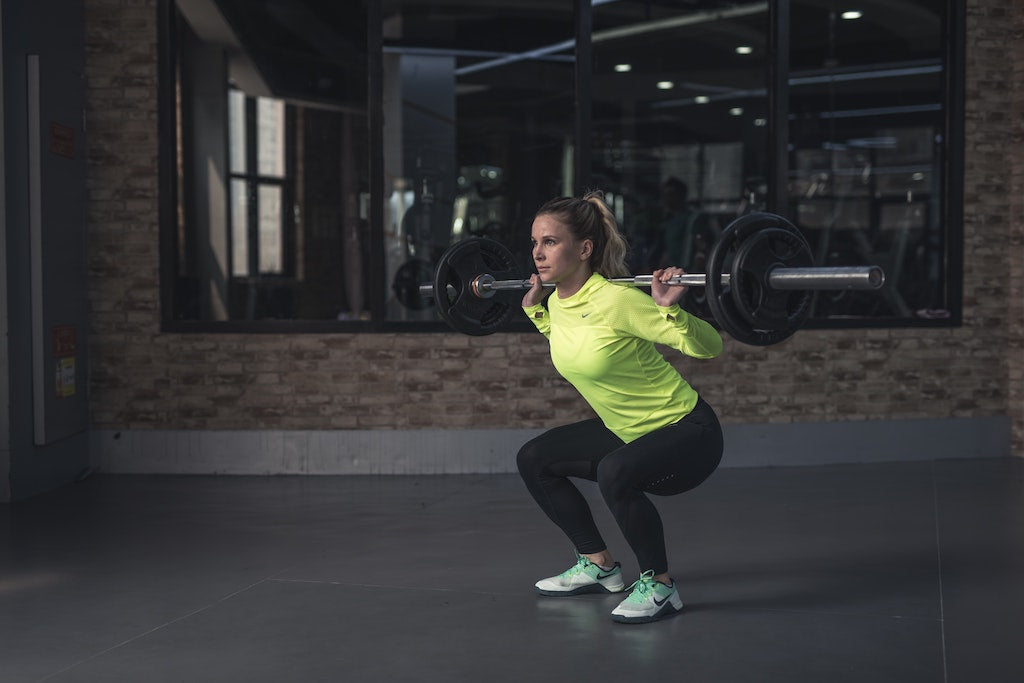 woman doing a barbell back squat with proper form