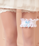 Trasparenze Sposa - lace leg garter in white or cream with a pale blue bow