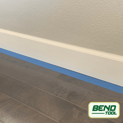 Bend Tool Co. - White profiled baseboard prepped with blue painters tape on hardwood floor