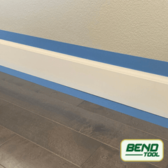 Bend Tool Co. - White profiled baseboard prepped with blue painters tape on hardwood floor and wall.