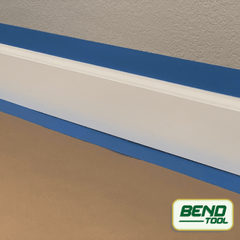 Bend Tool Co. - White profiled baseboard prepped with blue painters tape on hardwood floor and rosin paper