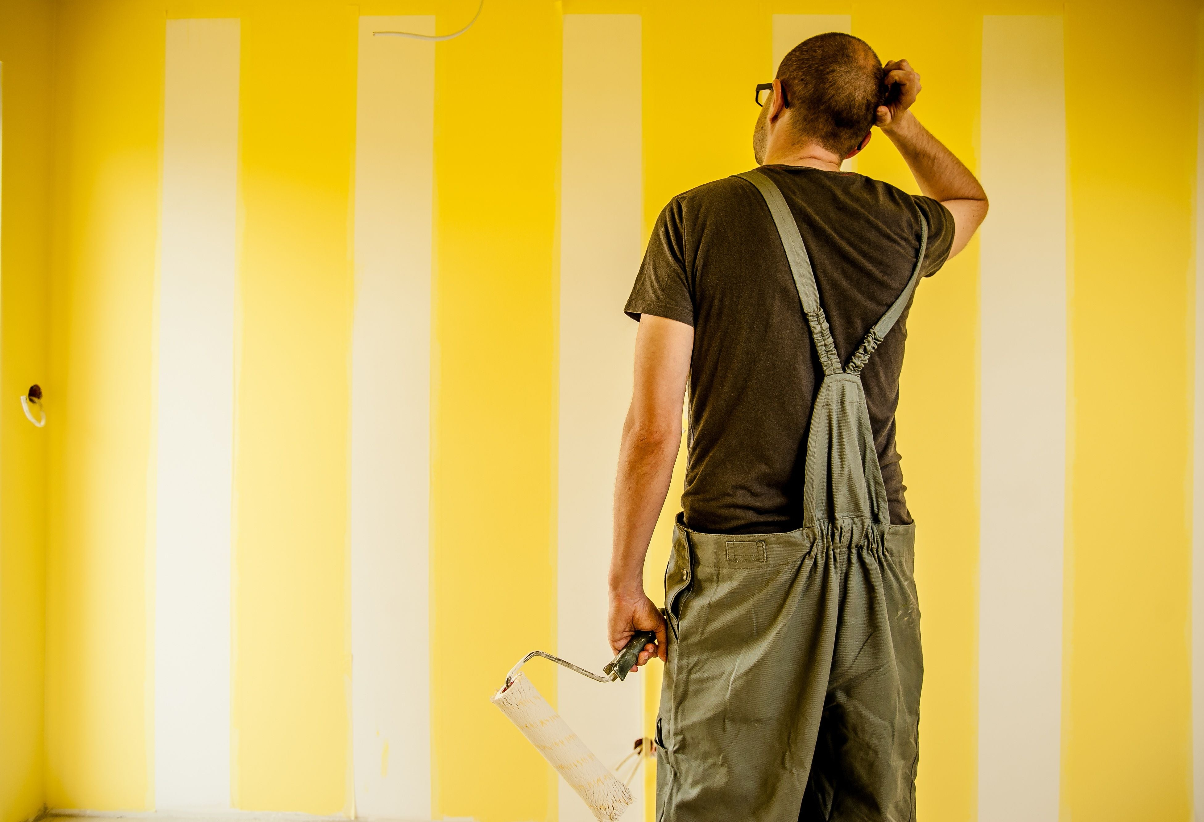 Man stares at the yellow wall where paint is in progress determing to paint baseboards or wall first. Bend Tool Co.