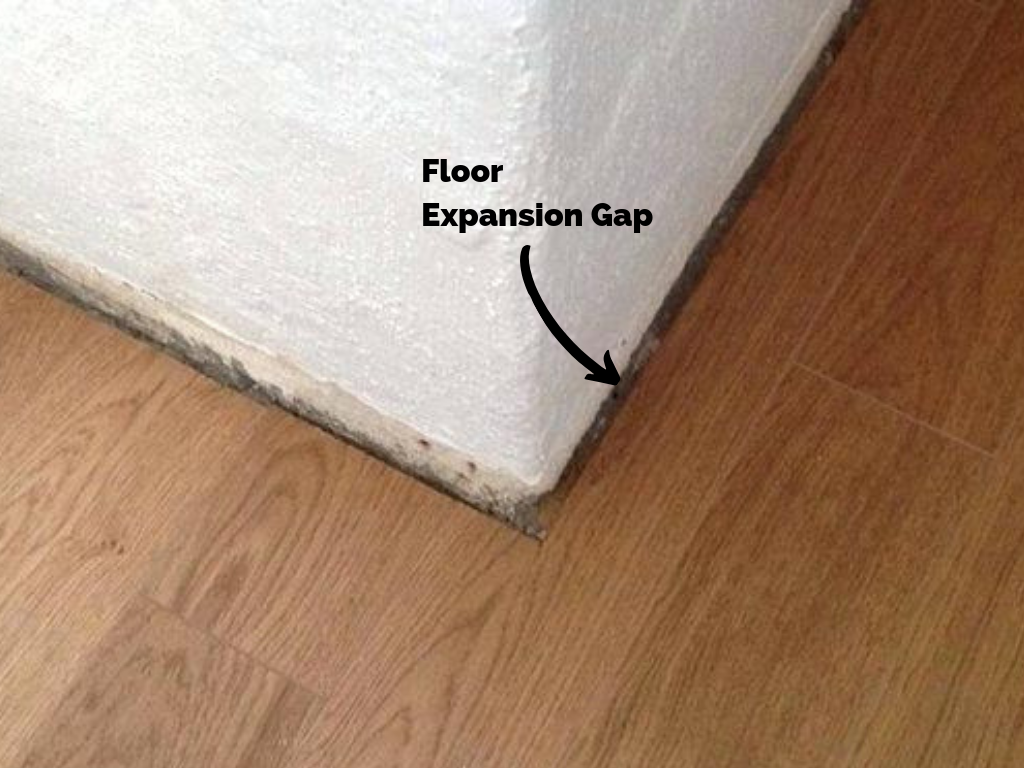 Hardwood floor 1/4'' expansion gap against drywall corner for baseboard trim installation.