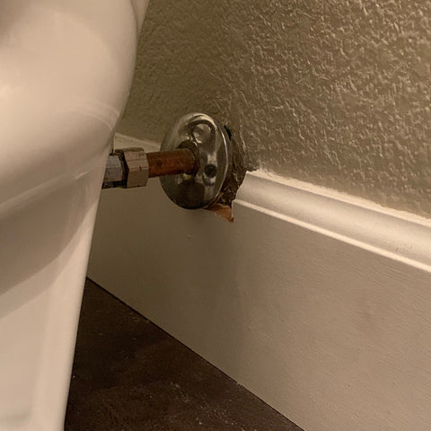 5 inch baseboard trim exceeds height of toilet supply line. Baseboard is cut around it, creating an unattractive look.