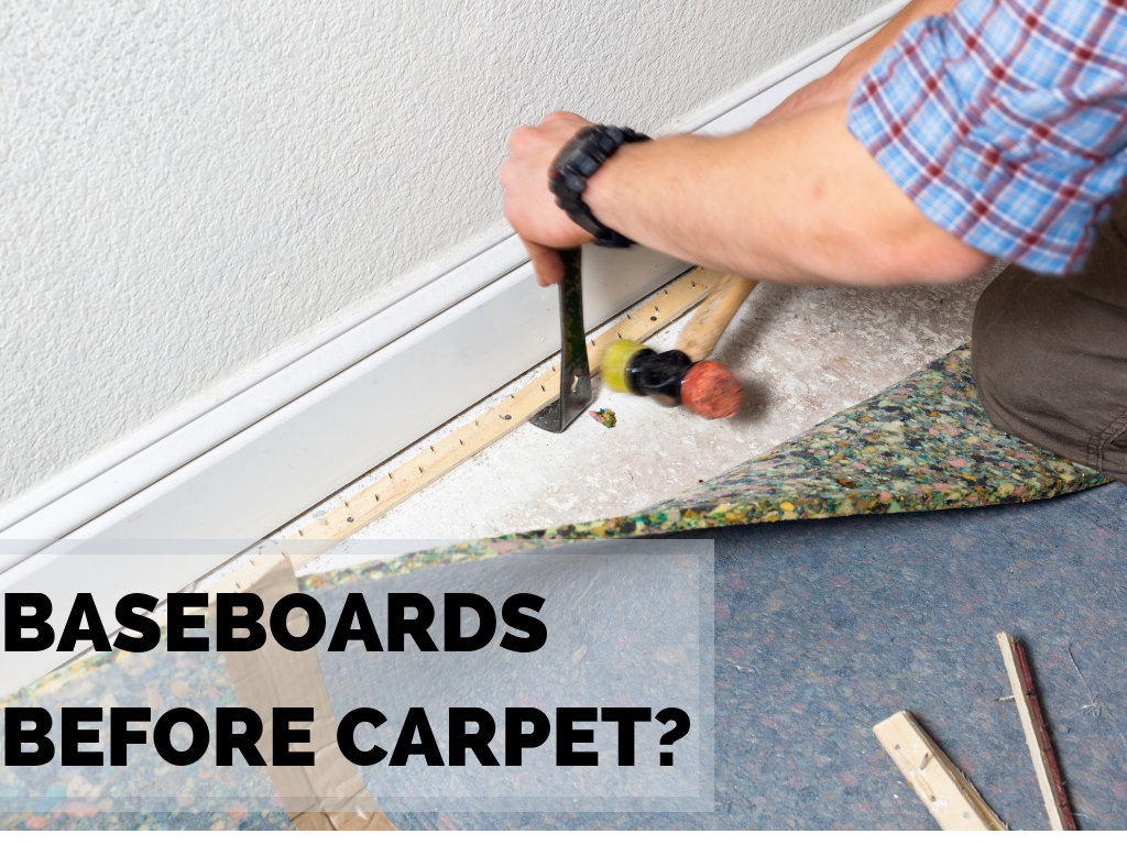 Baseboards before carpet? Carpet installer carefully removes tack strip against white baseboard with a claw hammer and small mallet.