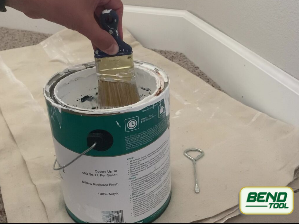 How to paint baseboards with carpet - tapping brush gently against paint can before applying