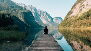 Man meditating on lake shore near mountains