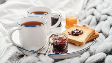 Tea cups and jam spread on bread