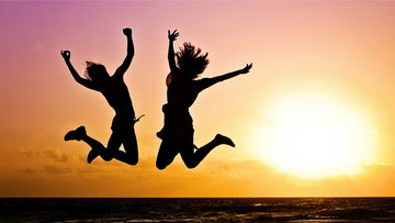 Two women jumping of joy in the sunset