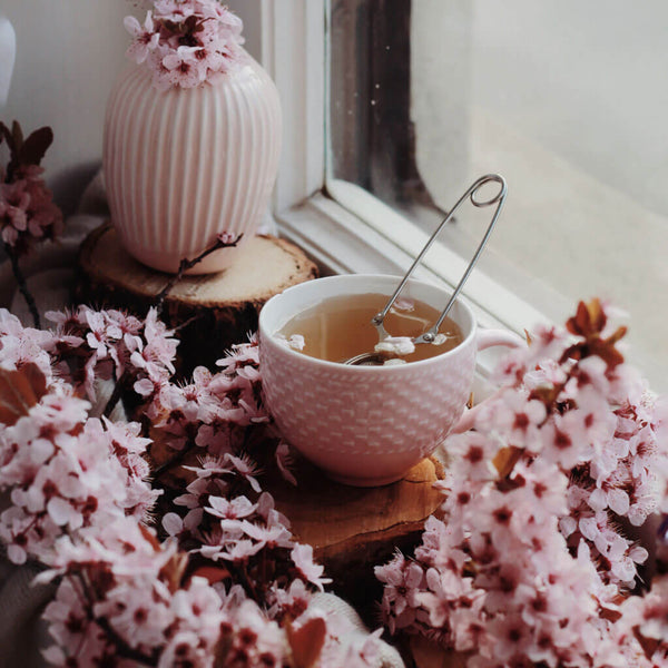 Cup with herbal tea and flowers near window